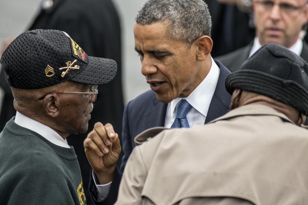 President Barack Obama talks with World War II veterans Sanders Matthews Sr., born 1921, left, and Lewis Coffield, born 1918, both Buffalo Soldiers, at Stewart Air National Guard Base in Newburgh, N.Y., Wednesday after delivering the commencement address at the United States Military Academy at West Point. The Associated Press