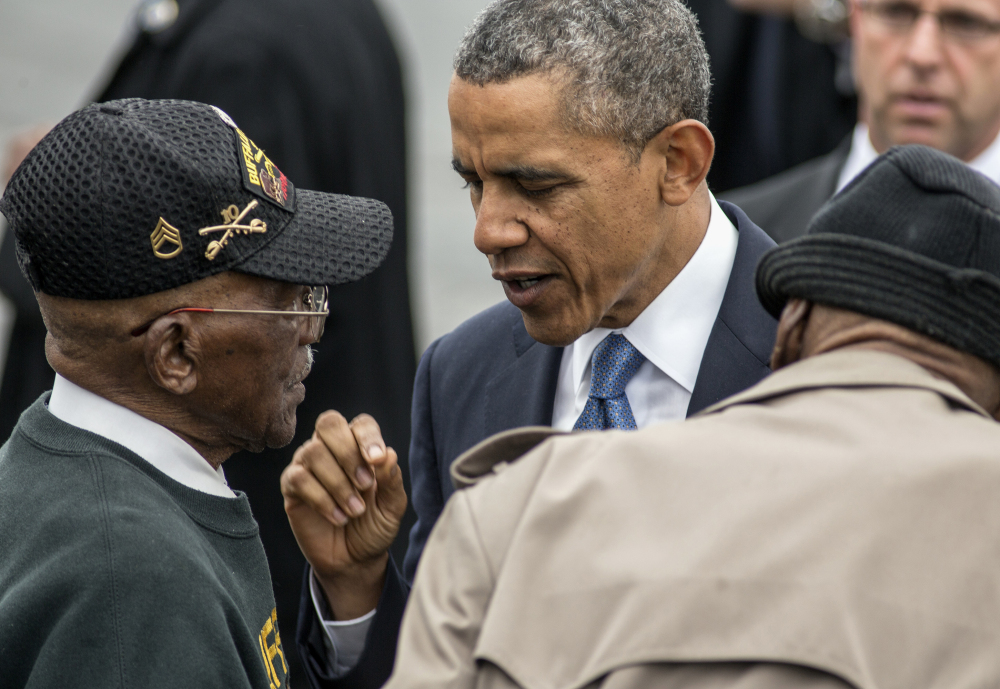 President Obama talks with World War II veterans Sanders Matthews Sr., born in 1921, left, and Lewis Coffield, born in 1918, both Buffalo Soldiers, after delivering the commencement address Wednesday at West Point. The Associated Press