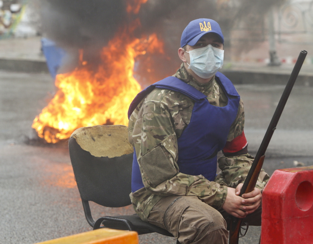 An activist sits near burning tires on Saturday in Independence Square in Kiev, Ukraine. Reuters