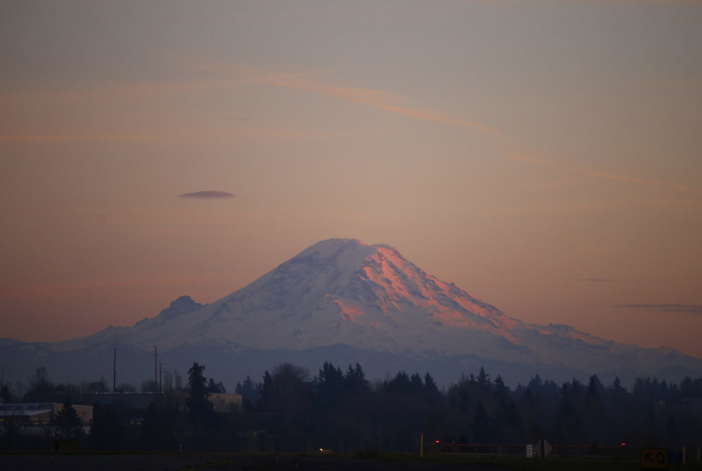 Mount Rainier is pictured as the last rays of sunlight hit its western side November 24, 2013. Two guides and their four clients are considered missing after they neither returned on schedule nor have communicated since the reached an altitude of 12,800 feet. The Associated Press