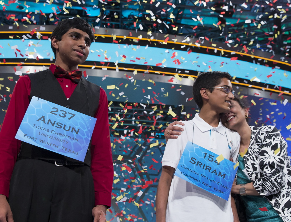Ansun Sujoe, 13, of Fort Worth, Texas, left, and Sriram Hathwar, 14, of Painted Post, N.Y., will share the title after Thursday's National Spelling Bee final in Oxon Hill, Md. The Associated Press