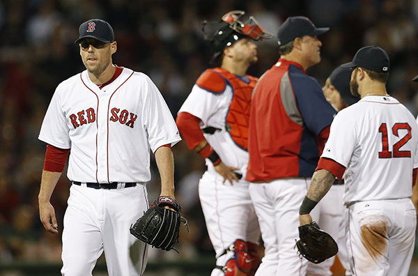 Boston Red Sox's John Lackey, left, walks to the dug out after being taken out by manager John Farrell, second from right, in the sixth inning of a baseball game against the Detroit Tigers in Boston, Saturday, May 17, 2014. The Associated Press