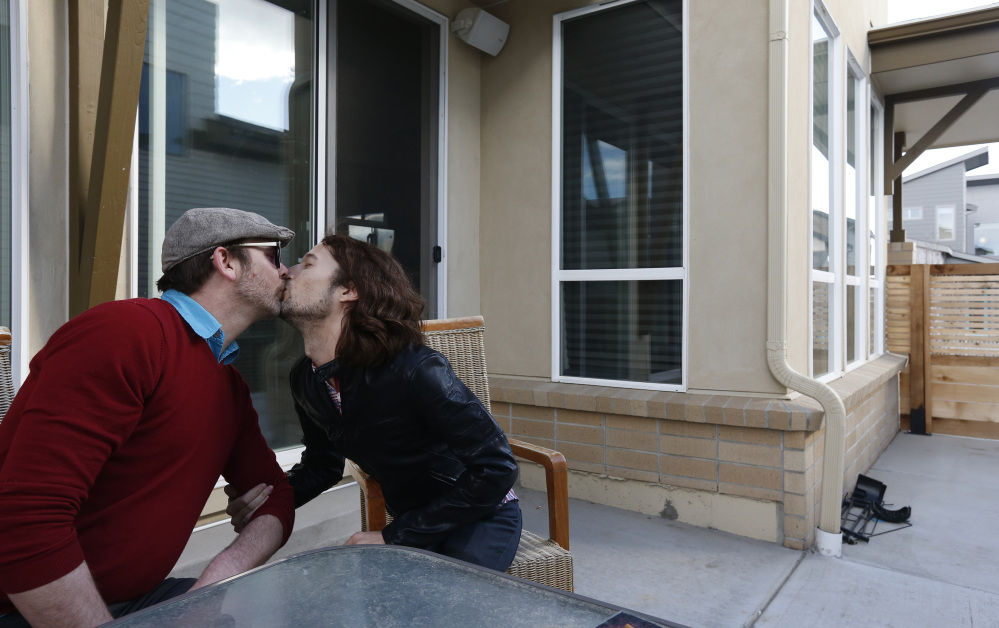 In this March 13, 2014 photo, Dave Mullins, right, kisses his husband Charlie Craig, on the patio of their home in Westminster, Colo. The couple filed a legal complaint with the Colorado Civil Rights Commission against a  Denver-area baker who refused to make a wedding cake for the two men, based on his religious beliefs. The baker, Masterpiece Cakeshop owner Jack Phillips, is appealing a ruling by a judge in December 2013 which upheld the complaint, and orders the baker to serve gay couples despite his religious beliefs or face fines. The Associated Press/Brennan Linsley