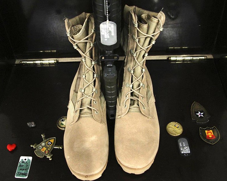 In this file photo medals and other items surround the boots of Christopher Gelineau. The items were left by soldiers of the 133rd Engineer Battalion as they paid their last respects at the end of a memorial service. 2004 Telegram File Photo/Gregory Rec