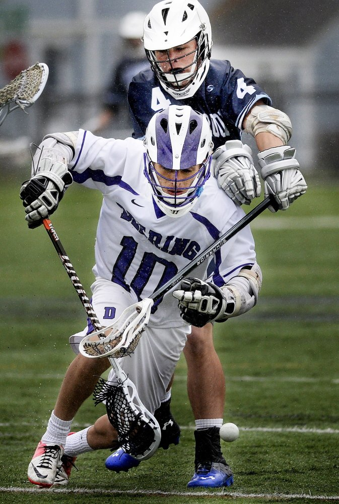 Sam Carroll of Westbook uses his stick to knock the ball away from Christian Castaneda of Deering.