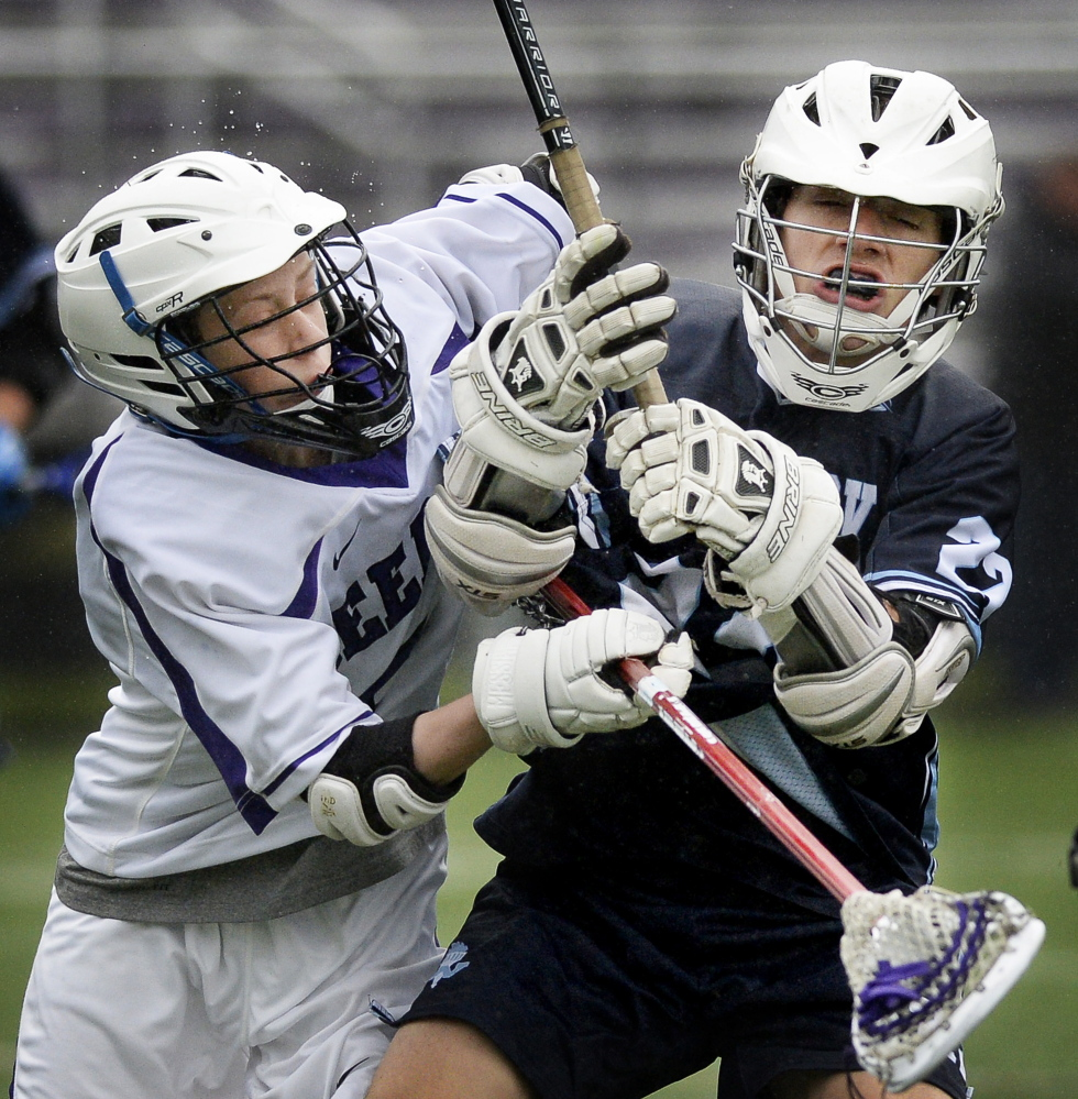 Photos by Shawn Patrick Ouellette/Staff Photographer Chase Walter of Deering, left, puts a check on Tyler Jack of Westbrook during their schoolboy lacrosse game Wednesday. Westbrook earned a 22-5 victory.