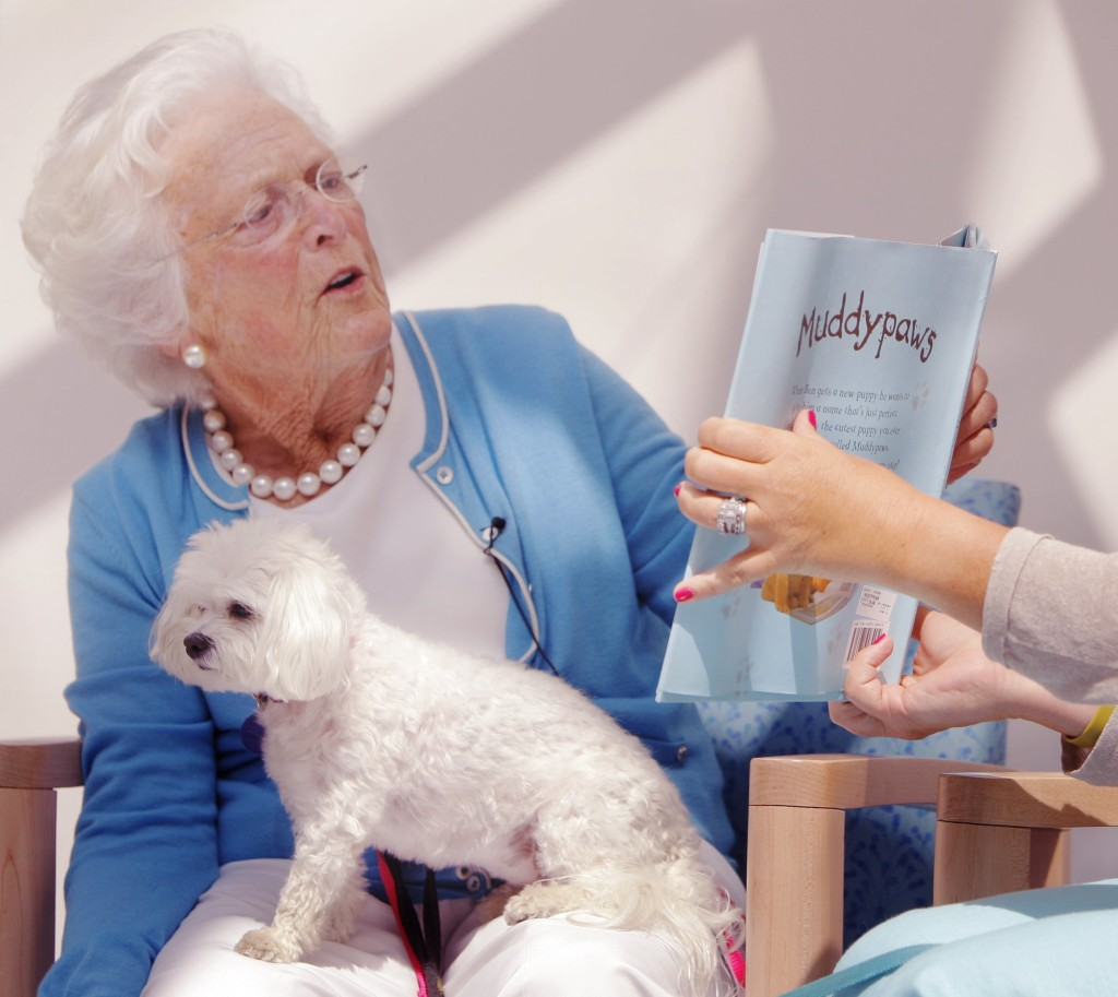"In this July 2012 photo, Barbara Bush reads the book ""Muddypaws"" to children at the Barbara Bush Children's Hospital at Maine Medical Center in Portland. In her lap is her dog Mini-Me."