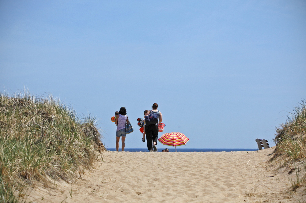 A family heads for the sand at Old Orchard Beach last month, on a day when temperatures climbed to near 80 degrees. Amelia Kunhardt/Staff Photographer