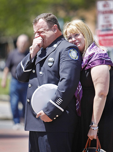 Portland Fire Lt. Dean Berry of Scarborough and his wife, Christa, weep as the casket of Portland Fire Capt. Michael Kucsma is brought out of the Cathedral of the Immaculate Conception following his funeral service in Portland Saturday. Jill Brady/Staff Photographer