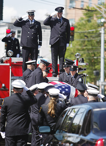 The casket carrying Portland Fire Capt. Michael Kucsma is brought down from Engine 2 before his funeral service at the Cathedral of the Immaculate Conception Saturday. ill Brady/Staff Photographer
