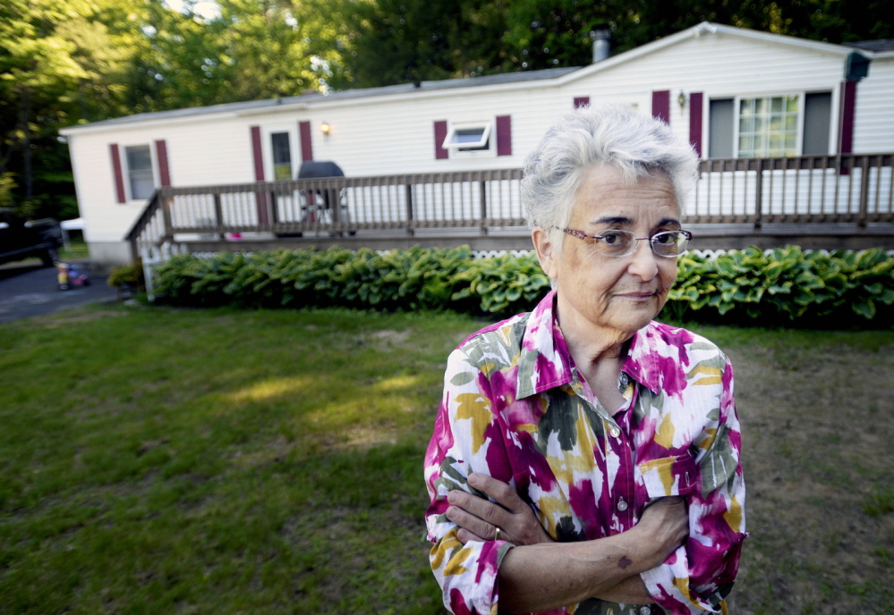 Deborah Nielsen stands outside her home in Buxton, where she was assaulted and tied up after interrupting a burglary in April. Even though charges against three suspects have been dropped, she says she still has faith in the police. Shawn Patrick Ouellette/Staff Photographer