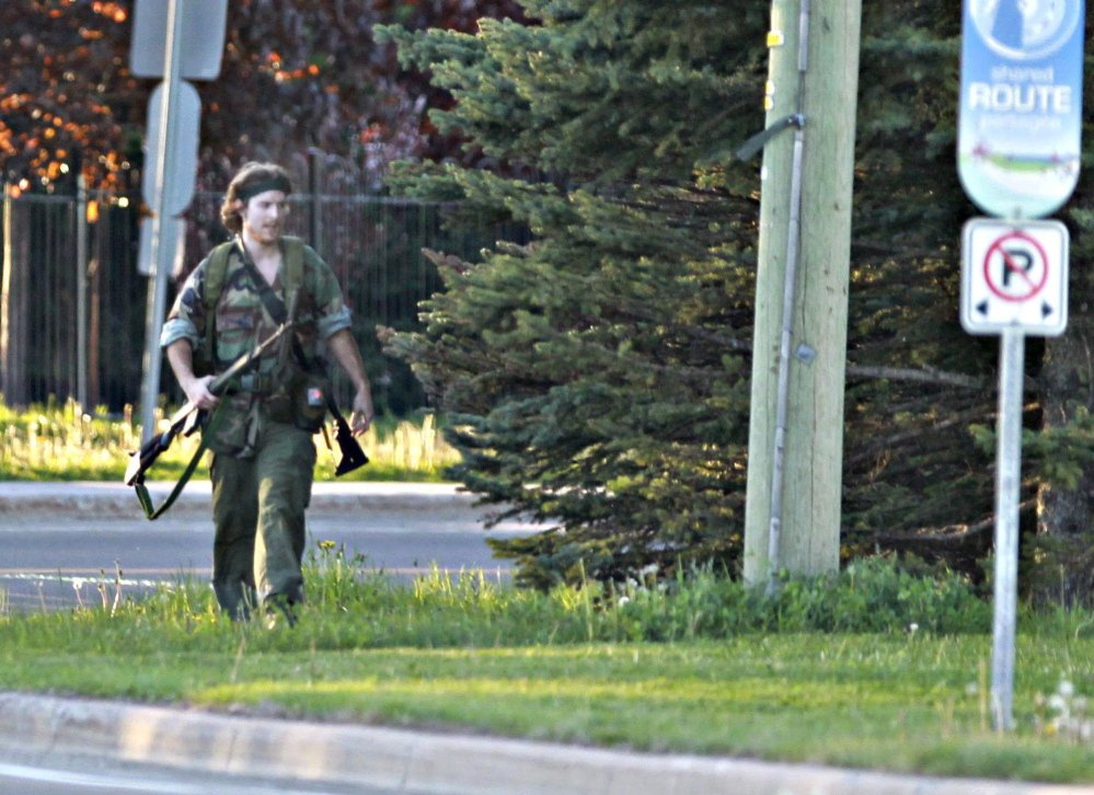A heavily armed man whom police have identified as Justin Bourque walks on a street in Moncton, New Brunswick, on Wednesday after shots were fired in the area. The man is suspected of killing three Royal Canadian Mounted Police officers. The Associated Press/The Canadian Press, Moncton Times & Transcript, telegraphjournal.com, Viktor Pivovarov