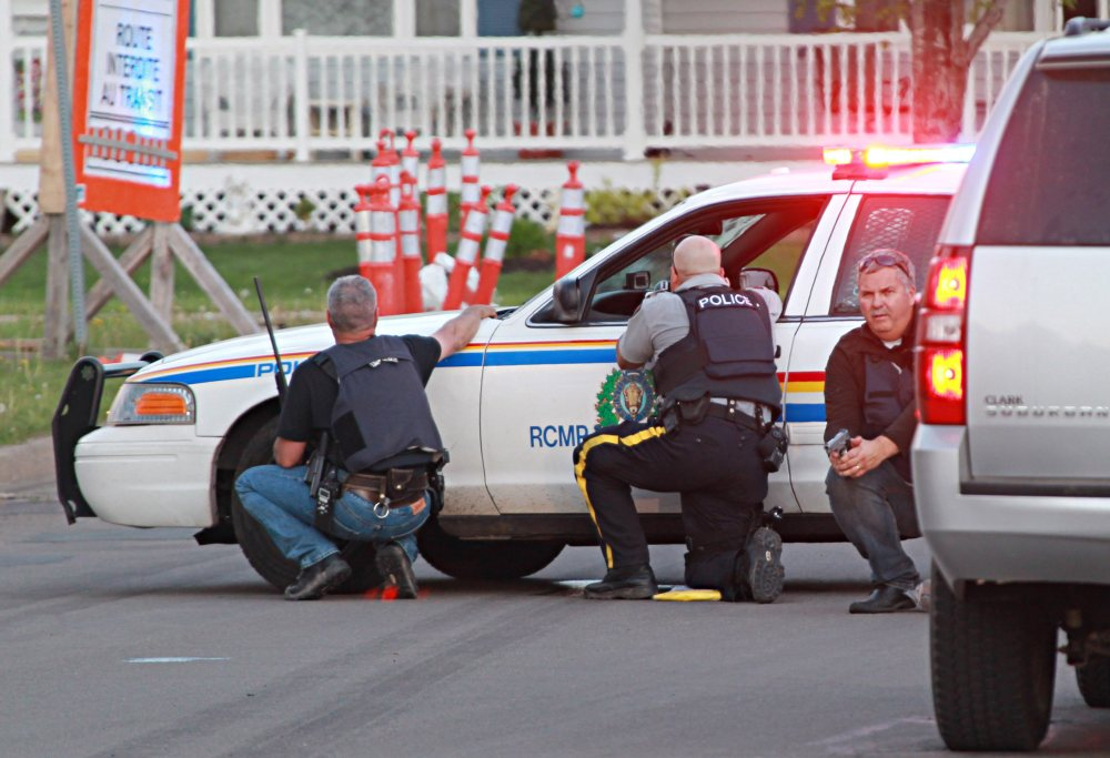Police officers take cover behind their vehicles at the scene of shootings Wednesday in Moncton, New Brunswick. The Associated Press / Moncton Times & Transcript, Ron Ward via The Canadian Press
