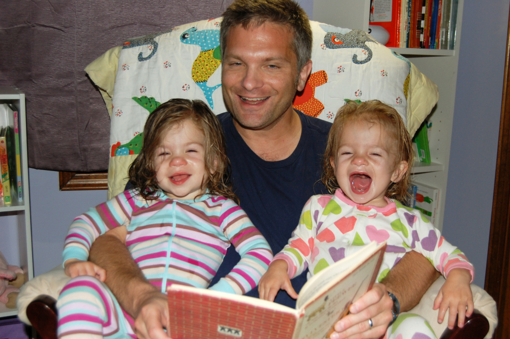 Mike Brandfon reads with his daughters Abby, left, and Sophie in Chicago. The number of U.S. fathers home with their kids full time for a variety of reasons is down from a peak 2.2 million in 2010, the official end of the recession, to about 2 million in 2012, according to a report released Thursday by the Pew Research Center. 2012 Photo/The Associated Press/Sara Brandfon