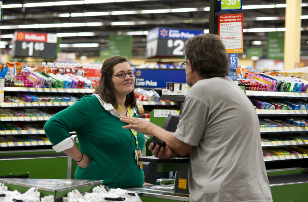 Cashier Candance Jones speaks Thursday with customer Bill Watson at the Wal-Mart Neighborhood Market in Bentonville, Ark. Wal-Mart's supercenters still account for 80 percent of its 4,000-plus U.S. stores, but the retailer is opening smaller outlets that cater to shoppers looking for more convenience. The Associated Press