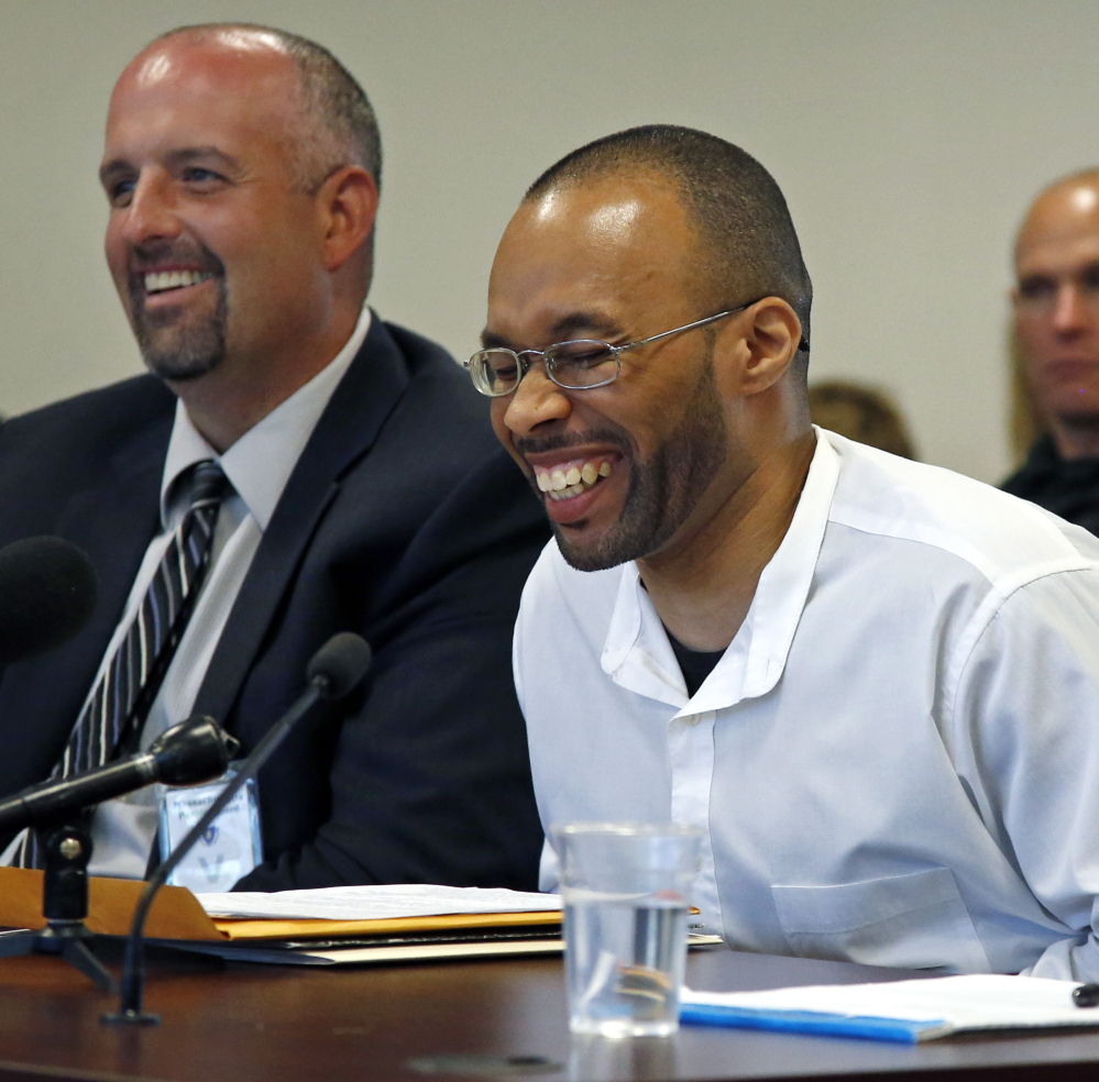 Imprisoned for 20 years, Frederick Christian, right, laughs during a light moment at a recent parole hearing in Natick, Mass. At left is his attorney Joe Mulhern. The Associated Press
