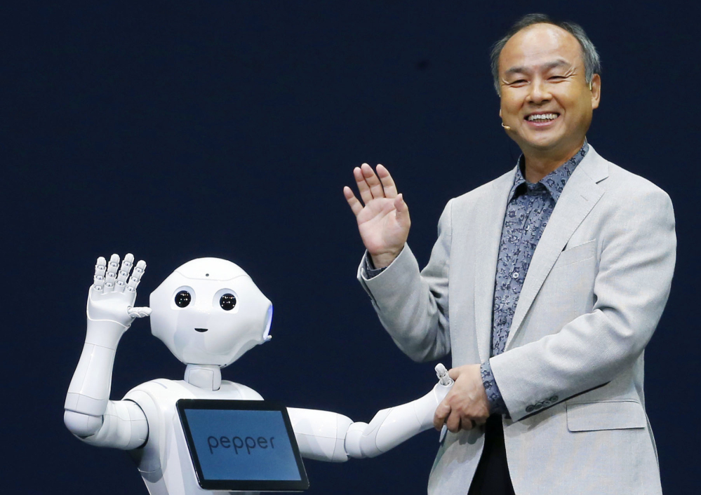 Softbank Corp. President Masayoshi Son and Pepper, a newly developed robot, wave together during a press event Thursday. The humanoid on wheels can decipher human emotions. AP Photo/Kyodo News