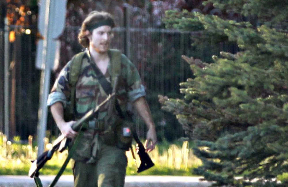 An armed man identified by police as Justin Bourque, suspected of killing three Royal Canadian Mounted Police officers, is seen in Moncton, New Brunswick. He was arrested early Friday. AP Photo/Moncton Times & Transcript, telegraphjournal.com, Viktor Pivovarov