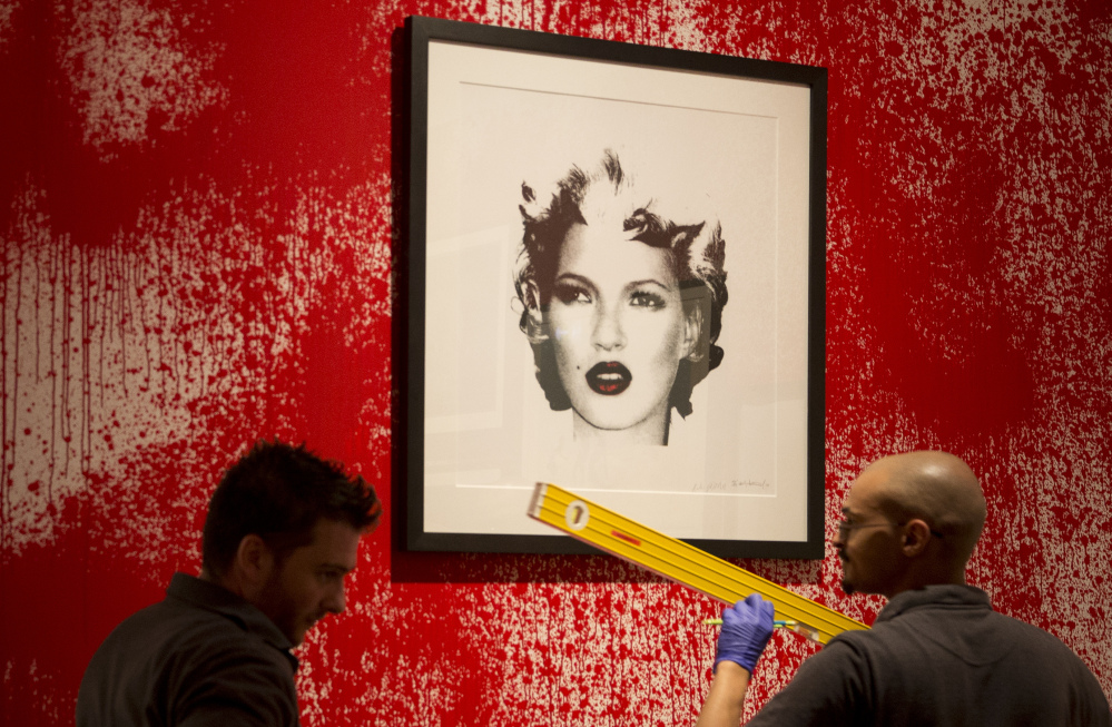 Sotheby's employees organize Banksy art Friday during a preview of an