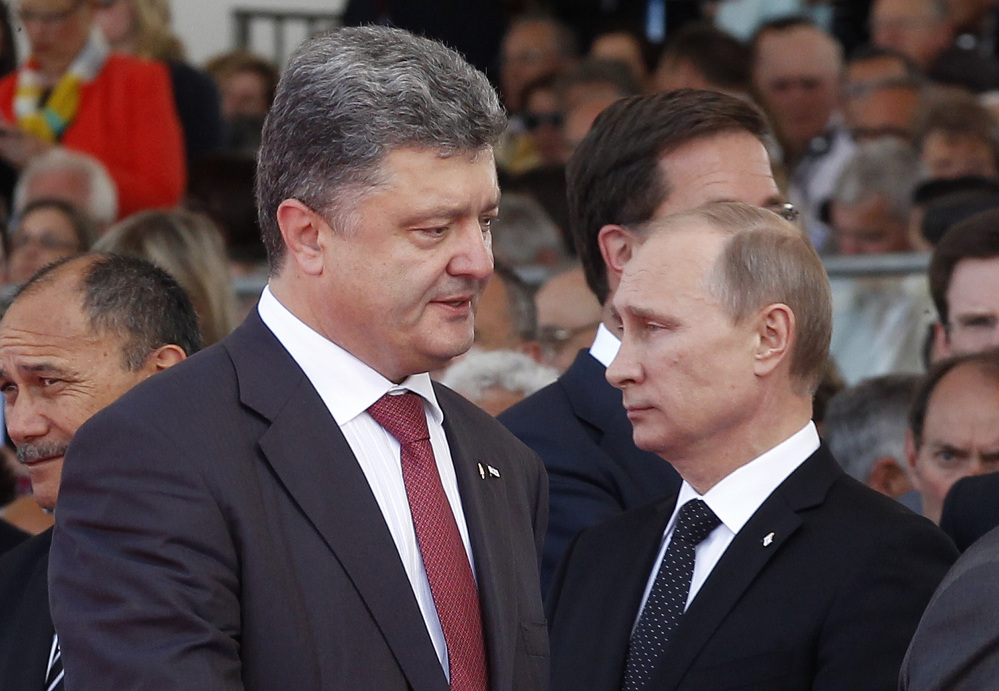 Ukraine President-elect Petro Poroshenko, left, walks past Russian President Vladimir Putin at Friday's commemoration of the 70th anniversary of D-Day in Ouistreham, France. The Associated Press