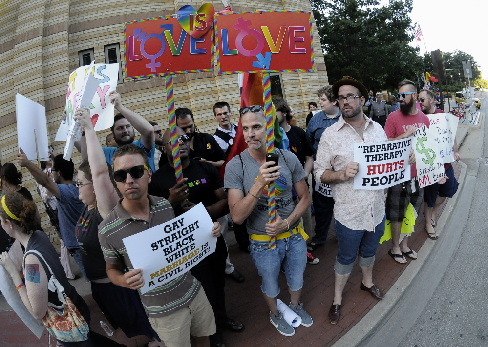 People hold signs during a same-sex marriage rally outside the Fort Worth Convention Center in Fort Worth, Texas, as the Texas Republican convention began Thursday. The Associated Press