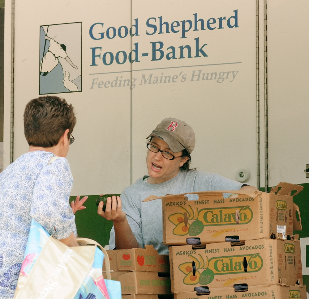 Jamee Luce talks to a client as she hands out avocados and tomatoes at the Good Shepherd Food-Bank's Food Mobile in Augusta. The organization distributed a record amount of food in 2014.