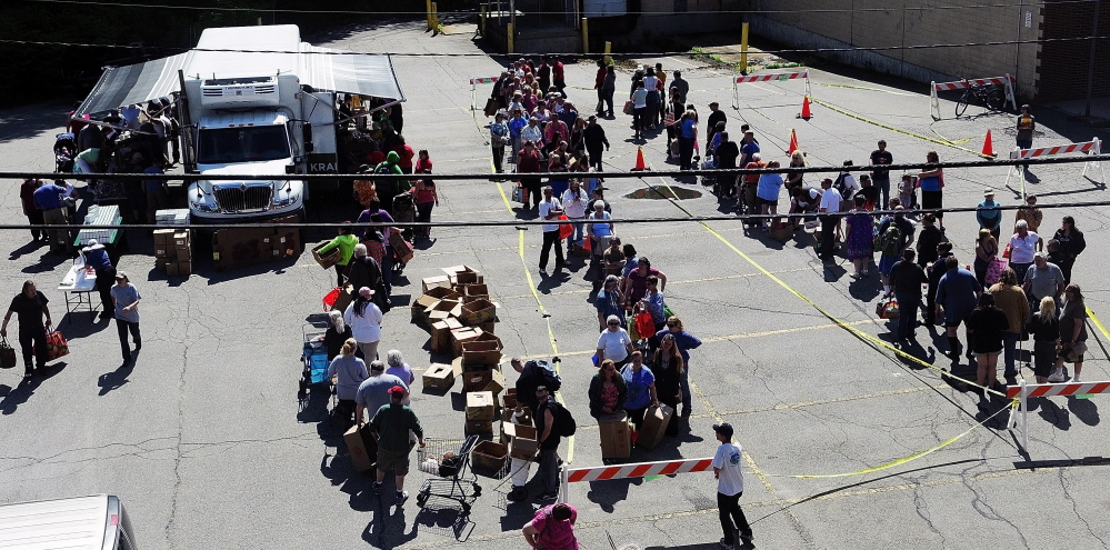 Photos by Joe Phelan/Knnebec Journal A line forms for the Good Shepherd Food Mobile on Friday on Willow Street in Augusta. There were no limitations on residency.