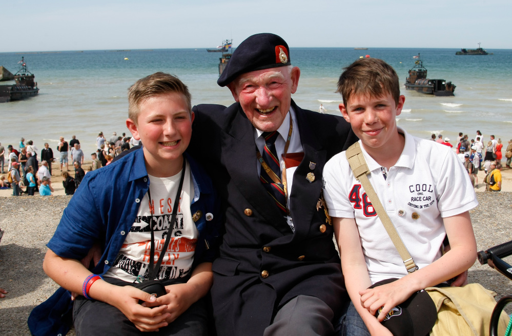 World War II veteran Reg Blake, 88, of London, who landed with the Royal Marines in Lion-sur-Mer on June 6, 1944, poses Friday with high school students Simon Legouge-Duval, left, and Adrien Sublin on the beach of Arromanches, France. The Associated Press