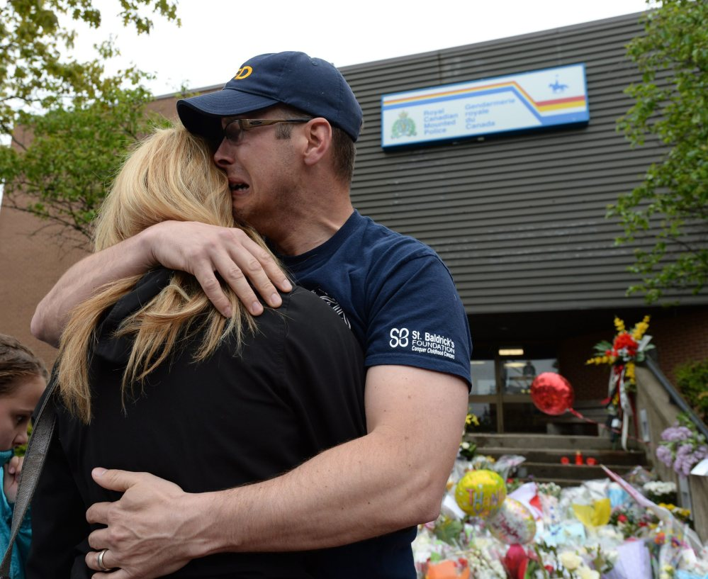 Jeff Pyke is comforted after placing flowers for his friend, Constable Douglas Larche, outside Royal Canadian Mounted Police headquarters in Moncton, New Brunswick, on Friday. The Associated Press
