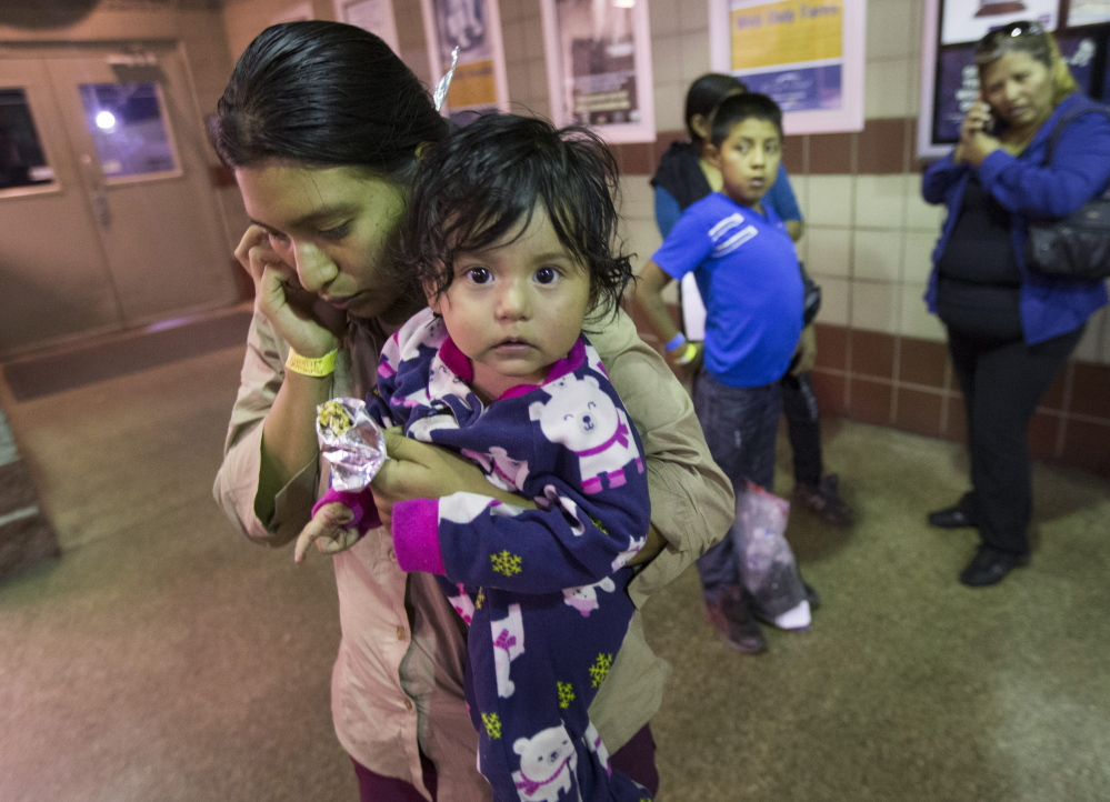 Judy Elizabeth Martinez of Guatemala holds her daughter Marjorie while calling family after being released at a Greyhound bus station in Phoenix by immigration officials on May 28. About 400 migrants were flown from Texas to Arizona on Memorial Day weekend. The Associated Press