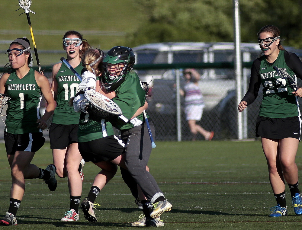 Waynflete's Ellen Silk and goalie Charlotte Majercik, center, embrace as Helen Gray Bauer (1), Amelia Deady (10) and Dana Peirce (22) join the celebration Friday after a 10-5 win over Cape Elizabeth in a Western Maine Conference girls' lacrosse season finale Friday. Gabe Souza/Staff Photographer