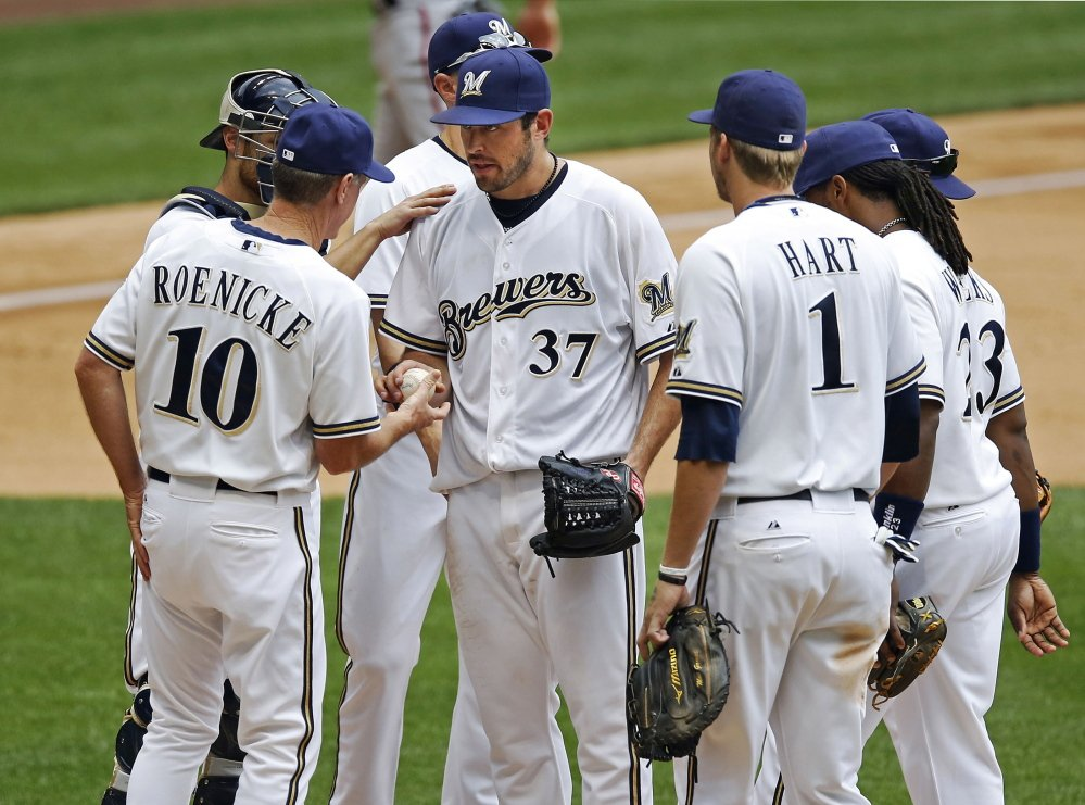 Mark Rogers, center, is removed by Brewers Manager Ron Roenicke in the sixth inning of a major league game in 2012. Two years later, Rogers' promising moment as a big-league pitcher finds him pitching in an independent league team after arm problems led Milwaukee to cut ties with him. 2012 File Photo/The Associated Press