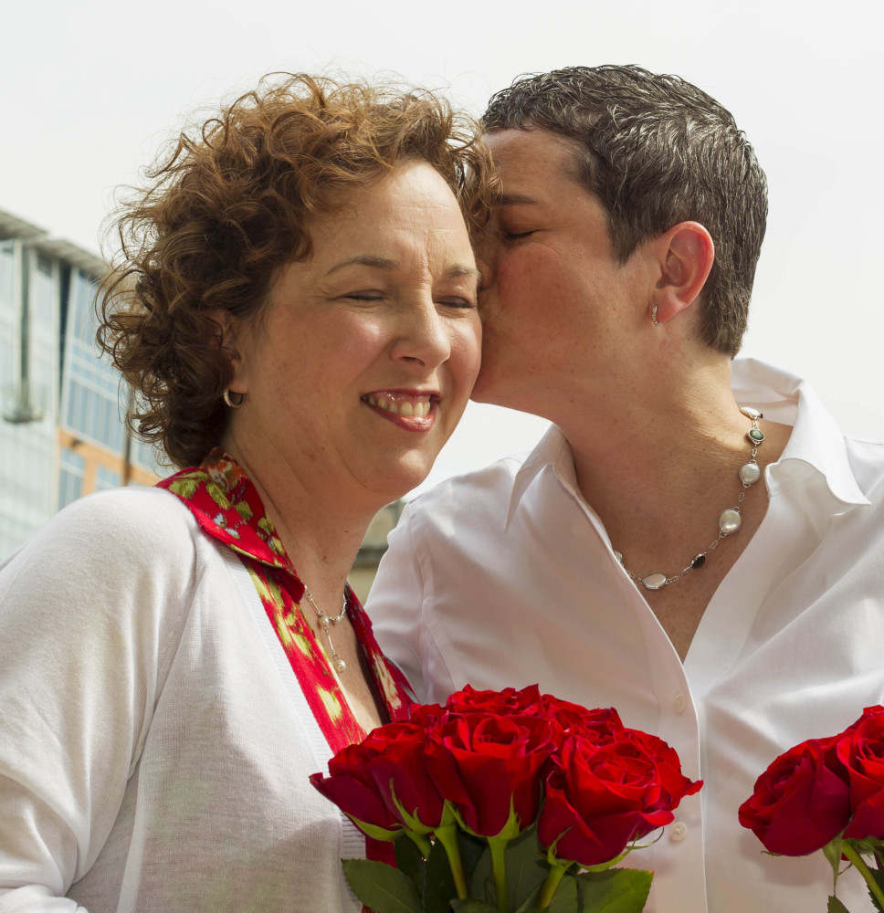 Kerry Lehman, right, kisses Sara Hinkel, after they wed Saturday in Madison, Wis. A judge struck down the state's ban on gay marriage Friday. The Associated Press