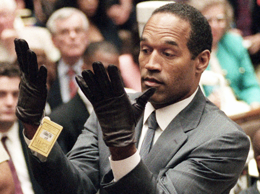 The Associated Press O.J. Simpson holds up his hands before the jury after putting on a new pair of gloves similar to the infamous bloody glove during his double-murder trial in Los Angeles on June 21, 1995. Associated Press writer Linda Deutsch is seen in the background at right; writer Dominick Dunne is in the background at left rear.