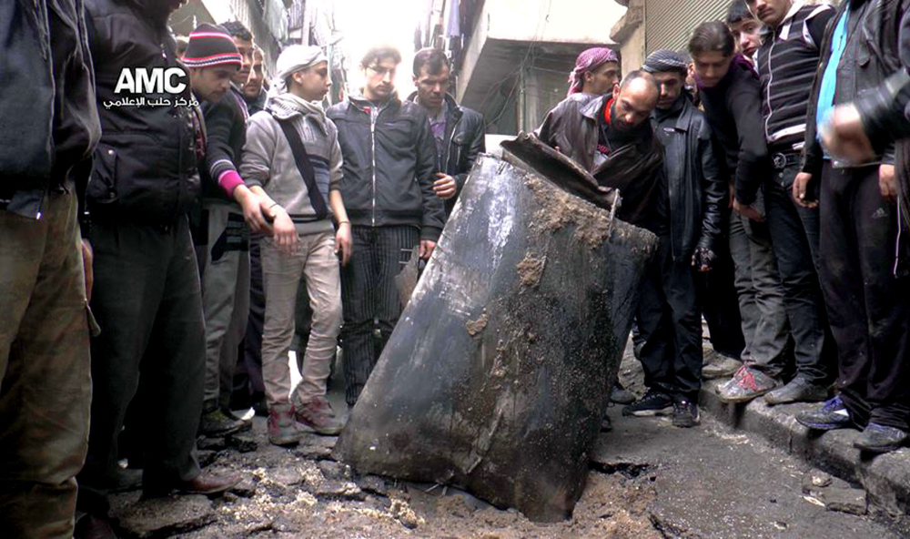 Syrians inspect an unexploded barrel bomb in January that reportedly was dropped from a government helicopter in Aleppo. Barrel bombs also have been used in Iraq and Sudan. The Associated Press