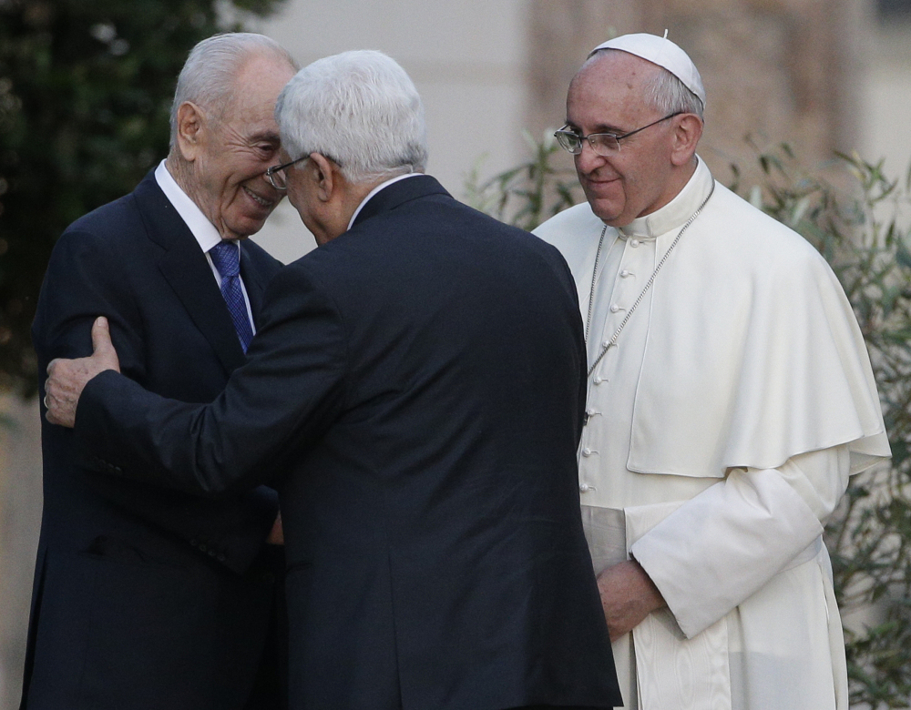 Pope Francis looks as Israel's President Shimon Peres, left, and Palestinian President Mahmoud Abbas embrace during an evening of peace prayers in the Vatican gardens on Sunday. The Associated Press