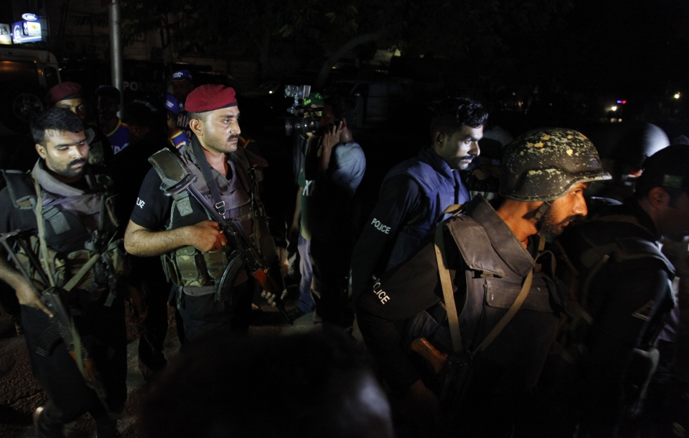 Pakistani commandos get ready to enter Karachi airport terminal following attacks by unknown gunmen on Sunday night, in Pakistan. Gunmen stormed an airport terminal used for VIPs and cargo in Pakistan's largest city on Sunday night, killing and wounding scores of people, officials said. The Associated Press