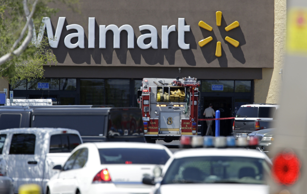Police and firefighters appear on the scene of a shooting at a Wal-Mart on Sunday in Las Vegas. Police say two suspects shot two officers at a Las Vegas pizza parlor before fatally shooting a person and turning the guns on themselves at a nearby Walmart. The Associated Press