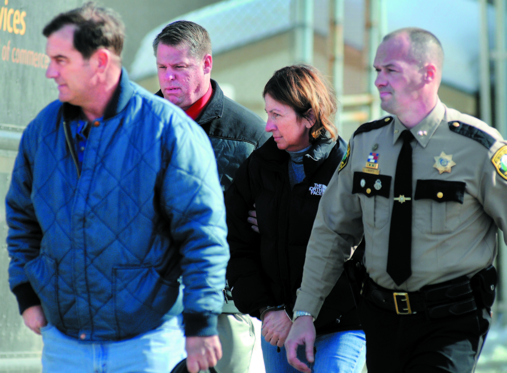 Former Chelsea Selectwoman Carole Swan, second from right, is led to the Kennebec County jail in handcuffs in 2011 after she was arrested at the sheriff's office in Augusta. Swan was accompanied by, from left, her husband, Marshall Swan, after Detective David Bucknam and Sheriff Randall Liberty arrested her. Kennebec Journal File Photo/Andy Molloy