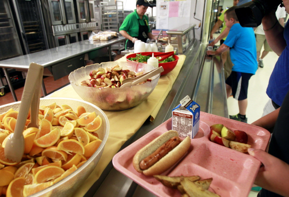 2013 File Photo/The Associated Press Students pick up their lunch at Barre Town Elementary School in Barre, Vt., last September. While new federal dietary standards for school lunches are a sign of progress and should not be dismantled, financially challenged school districts deserve extra time to meet their obligations.