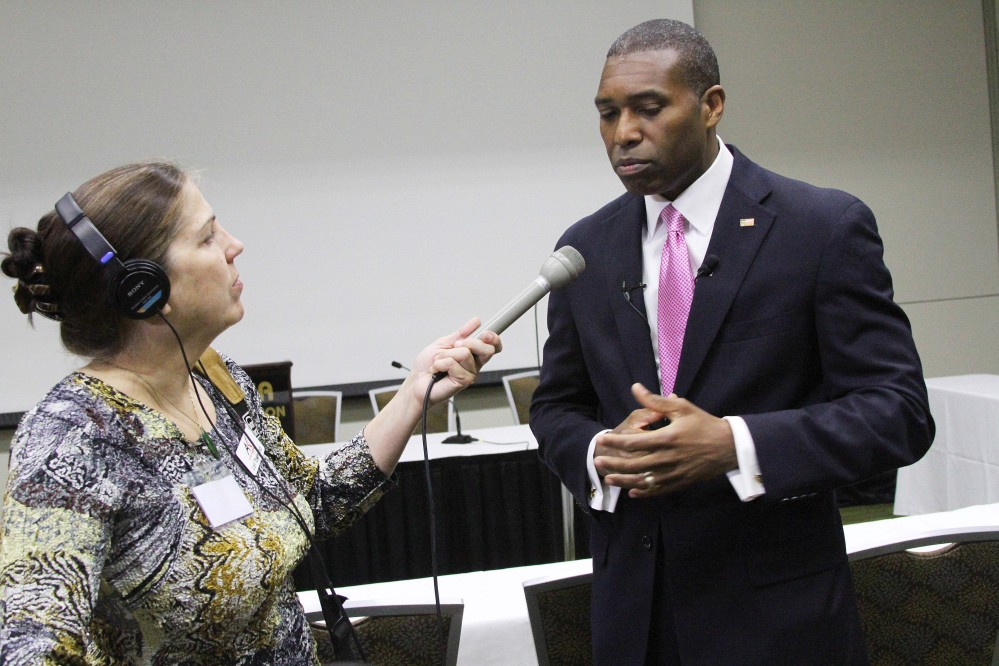 Associate U.S. Attorney General Tony West, right, speaks to reporters, including Lori Townsend with the Alaska Public Radio Network, left, about tribal voting rights on Monday, June 9, 2014, in Anchorage, Alaska. West updated delegates to the National Congress of American Indians on a plan announced earlier Monday by Attorney General Eric Holder, who will have his office consult with tribes across the country to develop ways to increase voting access for American Indians and Alaska Natives. The Associated Press/Mark Thiessen