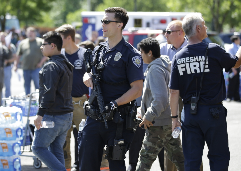 A police officer stands guard as students arrived by bus at a shopping center parking lot in Wood Village, Ore., after a shooting at Reynolds High School Tuesday, June 10, 2014, in nearby Troutdale. A gunman killed a student at the high school east of Portland Tuesday and the shooter is also dead, police said. (AP Photo/Rick Bowmer)