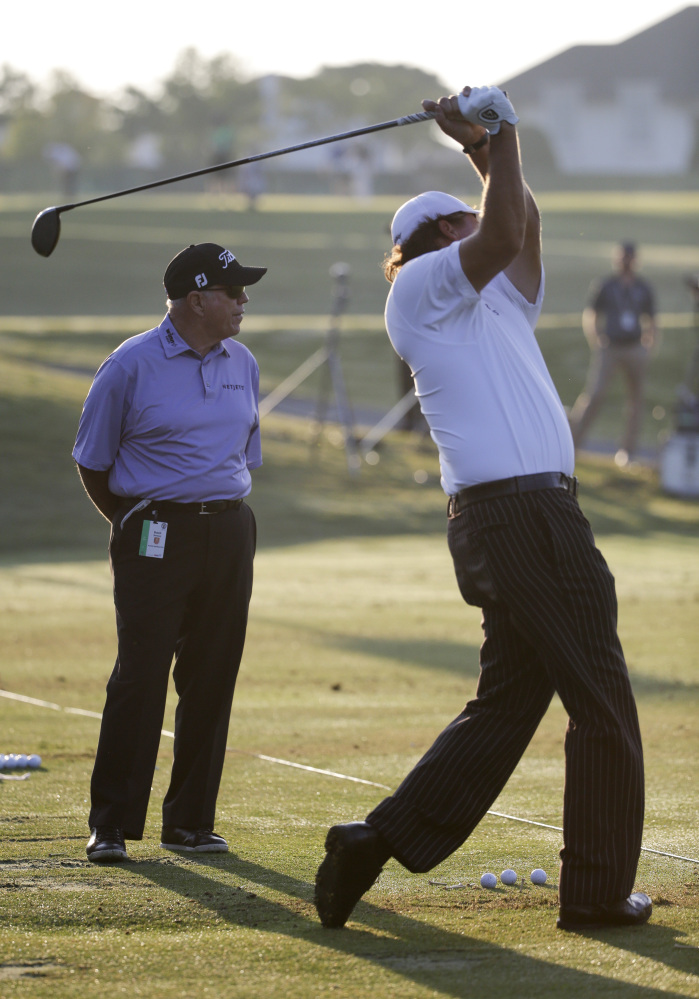 Phil Mickelson, right, hits as Butch Harmon watches on the practice tee before a practice round for the U.S. Open golf tournament in Pinehurst, N.C., on Tuesday. The tournament starts Thursday.
