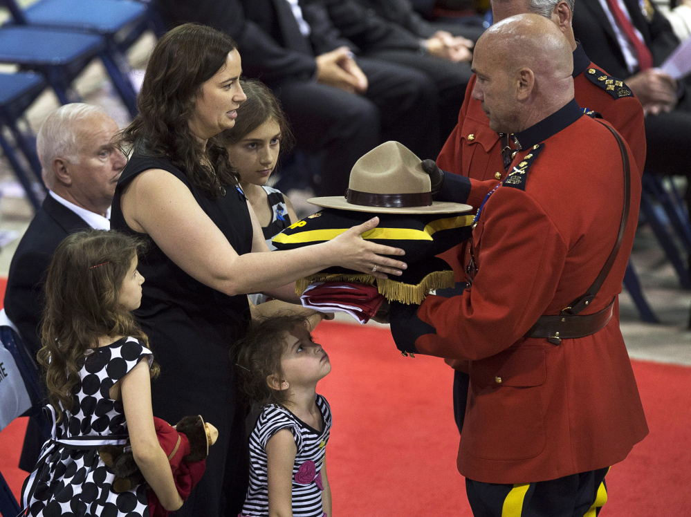 Nadine Larche, left, with her daughters Mia, Lauren and Alexa, receives the Canadian flag, and the Stetson and medals belonging to her husband, Constable Douglas James Larche, by Royal Canadian Mounted Police Commissioner Bob Paulson during the regimental funeral for Larche and two other officers at the Moncton Coliseum in Moncton, New Brunswick, on Tuesday, June 10, 2014. Constables David Ross, Fabrice Georges Gevaudan and Larche were killed in a shooting spree last Wednesday. Justin Bourque, 24, is facing three charges of first-degree murder and two charges of attempted murder. (AP Photo/The Canadian Press, Andrew Vaughan)