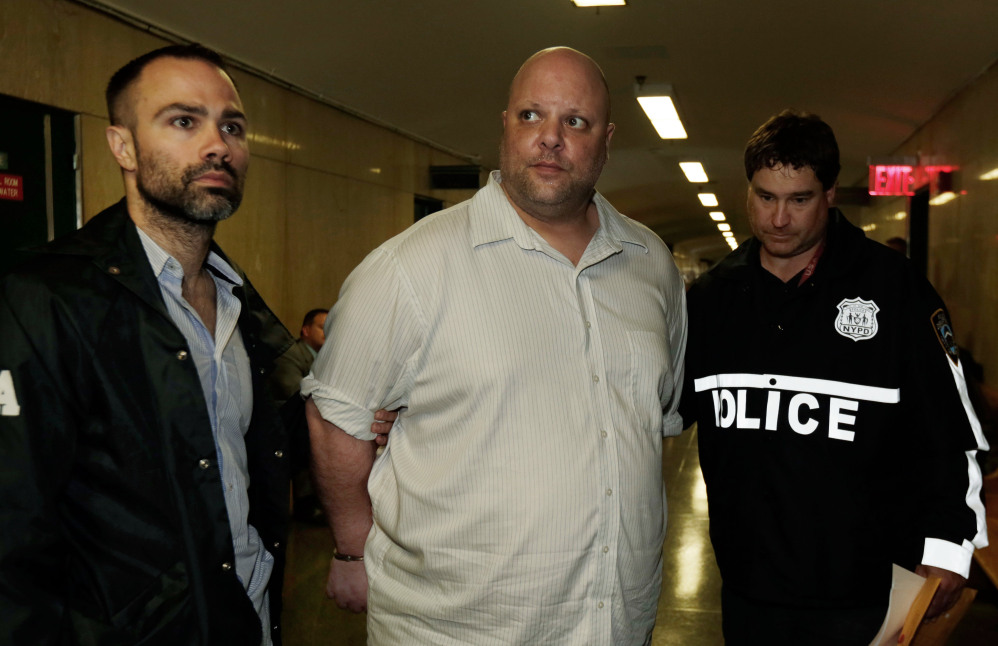 Carmine Vitolo, center, manager of a strip club in Queens, is escorted to court by police in New York, Wednesday.