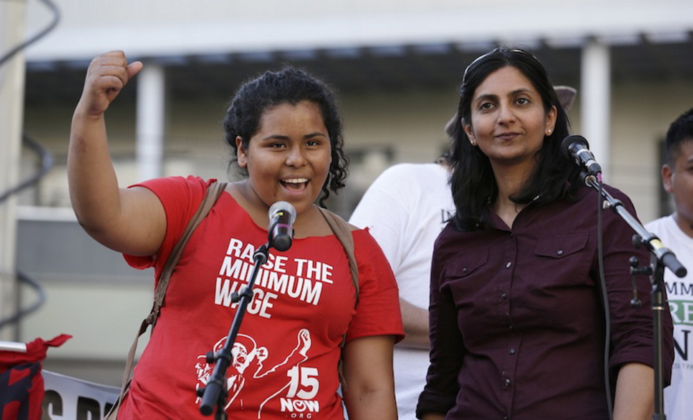 Stephanie Sucasaca holds up a fist at a rally in support of immigrant and workers rights and a boost in the minimum wage in Seattle on May 1. Seattle City Council Member Kshama Sawant is at right.