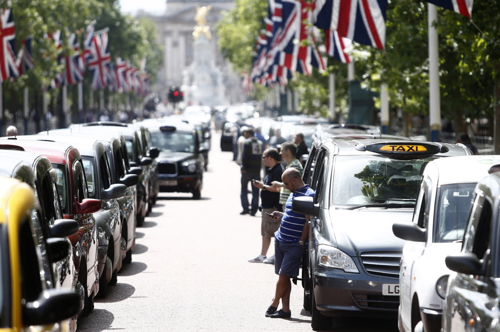London cabbies stand alongside parked taxis on The Mall, leading away from Buckingham Palace, during a protest against Uber Technologies' car sharing service on Wednesday.