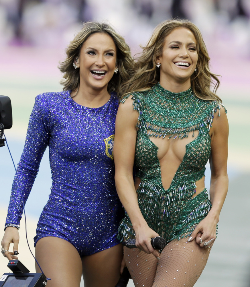 Brazilian singer Claudia Leitte, left and US singer Jennifer Lopez walk off the pitch after performing before the group A World Cup soccer match between Brazil and Croatia, the opening game of the tournament, in the Itaquerao Stadium in Sao Paulo, Brazil, Thursday, June 12, 2014.