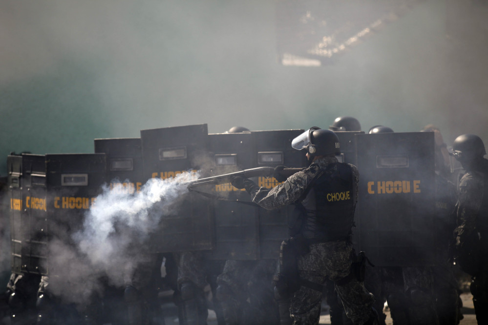 A Brazilian riot police aims at anti-World-Cup protester.