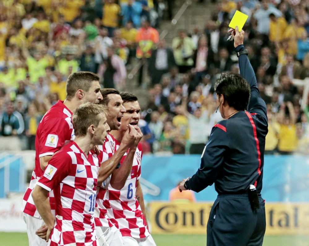 Croatia players argue after being given a penalty by referee Yuichi Nishimura from Japan during the group A World Cup soccer match between Brazil and Croatia, the opening game of the tournament, in the Itaquerao Stadium in Sao Paulo, Brazil, Thursday, June 12, 2014.